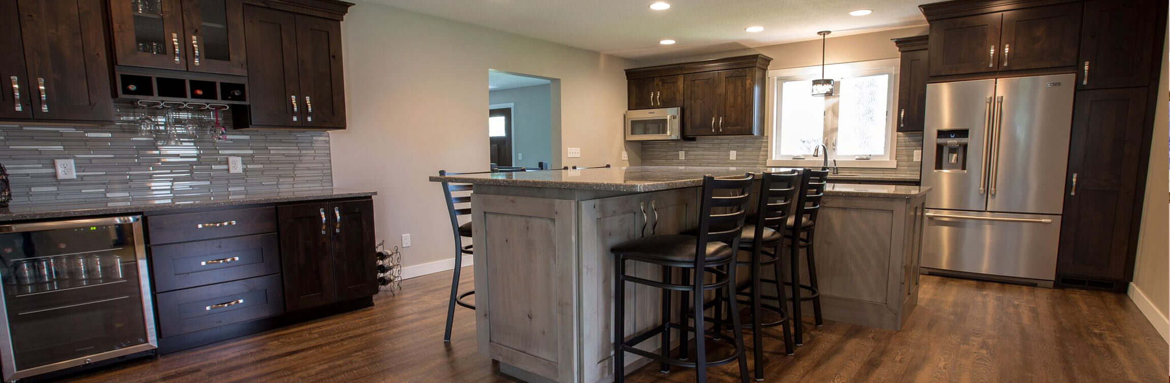 Custom Residential Kitchen & Bar Station featuring dark-stained solid wood cabinets, glass tile backsplash, large center island, stone countertops, and hardwood flooring